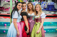 Attractive and joyful woamn at German Oktoberfest with traditional dirndl dresses and joyride in the background.