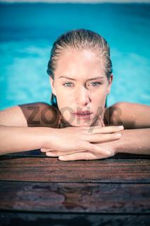 Portrait of beautiful woman leaning on poolside