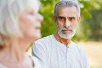 Alter Mann blickt nachdenklich auf seine Frau