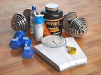 Fitness, bodybuilding or weight loss concept. Weight scales, dumbbells whey protein powder with shaker. Healthy lifestyle.