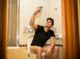 Smiling young man taking selfie while defecating