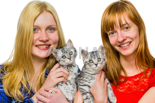 Two girls showing young silver tabby cats