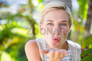 Pretty blonde woman smiling at the camera and blowing kiss