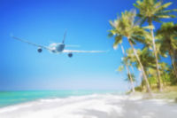 Blurred abstract travel concept. Airplane flying over tropical beach