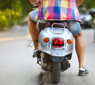 Rear view of young man riding scooter along the street