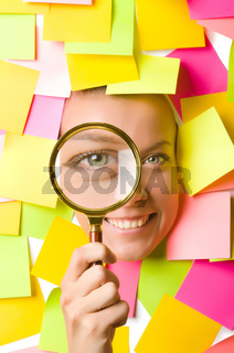Woman with reminder notes and magnifying glass