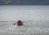 Nepalese woman paddling across Phewa Lake in Pokhara