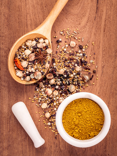 Assorted of spices  in wooden spoon  black pepper ,white pepper, black mustard,yellow mustard,fenugreek,cumin ,garlic and  fennel seeds with white mortar on teak wood background.
