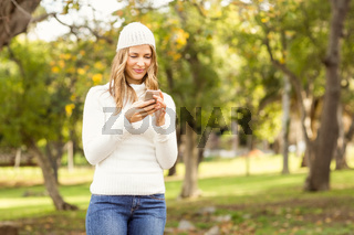 Smiling pretty woman texting with her smartphone