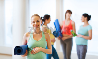 happy pregnant woman with mat in gym