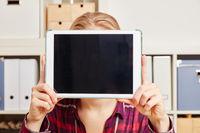 Frau hält Tablet Computer vor Gesicht