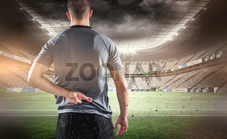 Composite image of rear view of rugby player with fingers crossed