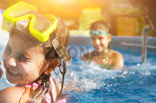 Children playing in pool. Two little girls having fun in the pool