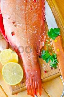 raw fish with aroma spice on wooden background