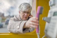 An elderly lady stands on smartphone in the ear at a phone booth and engages with his hand up the ph