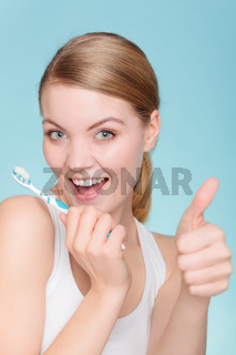 woman holds toothbrush with toothpaste cleaning teeth