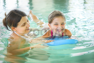 Mother learning to swim her little daughter in an indoor swimming pool