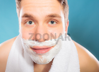 Young handsome man with shaving cream foam.