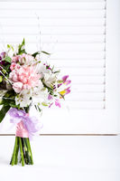 Pastel bouquet from pink and purple gillyflowers on white shutters background