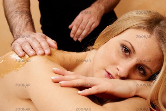 Young woman receiving an honey-salt-massage