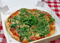 Vegetarische Pizza mit Rucola, Tomaten und Parmesan im Pappkarton