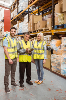 Warehouse team working together wile smiling at camera