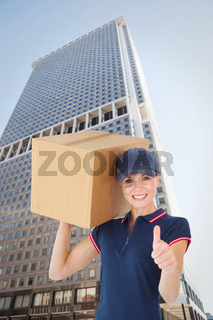 Composite image of happy delivery woman holding cardboard box showing thumbs up