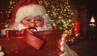 Closeup of Santa holding gift with Christmas scene in background