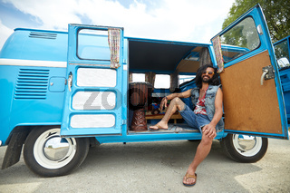 smiling young hippie man in minivan car