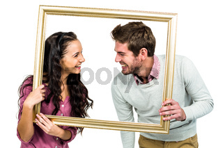 Stylish couple holding picture frame