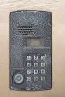 Electronic access control door box with numeric keypad closeup. Security intercom number keypad at apartment door.