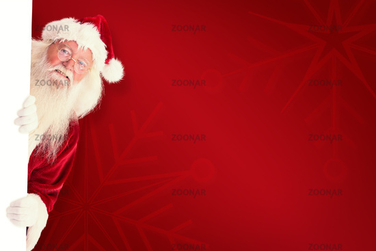 Composite image of santa looks out behind a wall