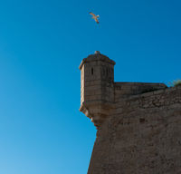 Turret against blue sky background. Castle of Santa Barbara in Alicante city. Spain