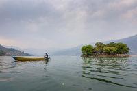 Nepalese man paddling on Phewa Lake in Pokhara