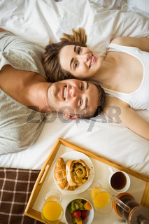 Cute couple having breakfast in bed