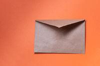 Brown Envelope  on orange background, copyspace.