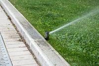 Sprinkler system working on fresh green grass