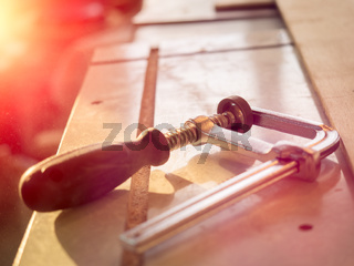 Real woodworking shop: clamps holding workpiece gluing, close-up