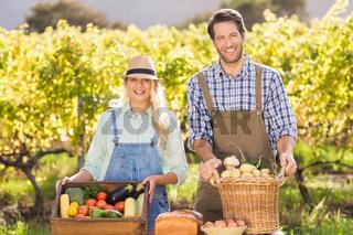 Happy farmer couple presenting their local food