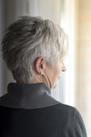 Rear view of an elderly lady with gray hair, looki