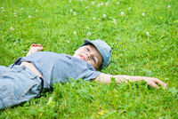 Little caucasian boy resting on grass