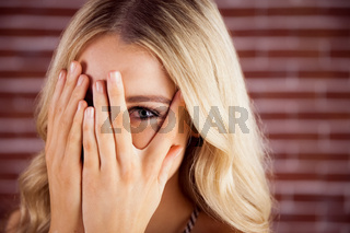 Beautiful blonde woman hiding behind hands