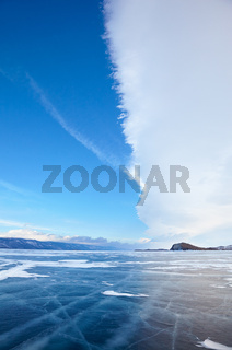 Winter ice landscape on lake Baikal with dramatic weather clouds front before the Storm