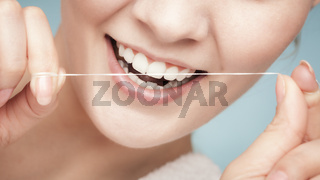 Girl cleaning teeth with dental floss. Health care