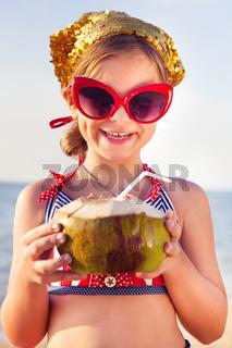 Little adorable girl drinking coconut milk on the beach