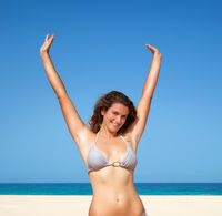 woman raised her hands up on the beach