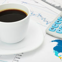 Coffee cup and calculator over world map and some financial charts - business concept