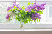 Lilac bouquet in vase on window