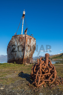 Rusty old whaler chained to iron post