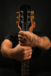 Man holding guitar neck with two hands isolated on black